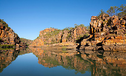 Stunning red sandstone cliffs are reflected in the still waters of the Sale River.