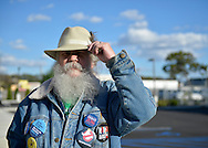 "Merrick, New York, USA. October 23, 2016. FRED S. CHANDLER, 66, of North Bellmore, wearing several political campaign buttons supporting Democratic presidential candidate Hillary Clinton, holds onto his hat in wind during rally to demand public water and stop New York American Water (NYAW) rate hike. On denim jacket included buttons for Hofstra University DEBATE 2016 - and ""So My Daughter Knows She Can Be President. Hillary 16"" - ""TRUMPBUSTERS"" - ""CLINTON KAINE 16"" - and Monopoly Man character with ""NEVER TRUMP"" text."