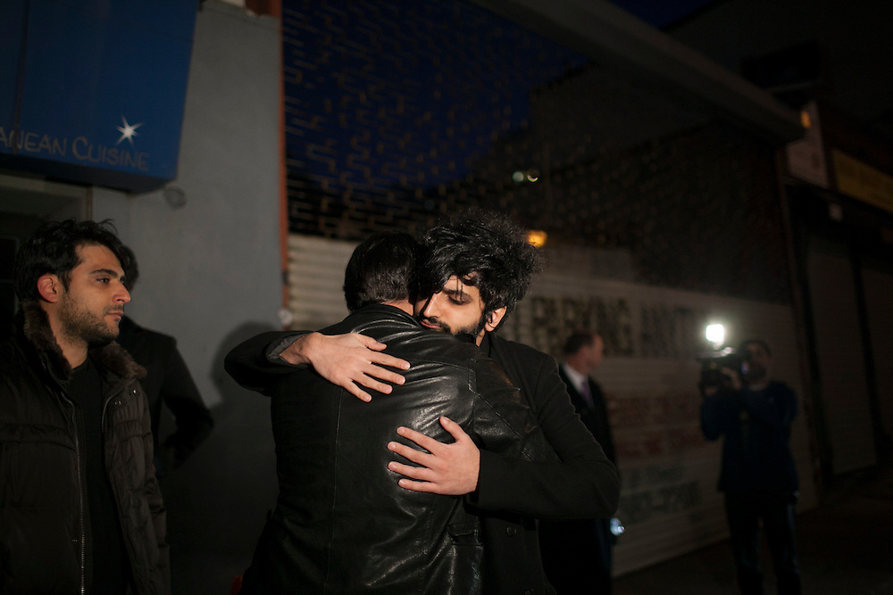 Yellow Dogs band member Koory Mirzaei, center right, receives a hug as he arrives to a candlelight vigil for the Yellow Dogs, the band whose members were killed last week, at Cameo Gallery, 93 North 6th Street in the Williamsburg neighborhood of Brooklyn, NY on Monday, Nov. 18, 2013.<br /> <br /> Photograph by Andrew Hinderaker