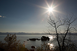 """""""Solar Eclipse Above Tahoe"""" - Photograph of the solar eclipse above Whale Rock at Lake Tahoe. You can't see the eclipse in the sun but you can see it happening in the lens flare on the bottom left of the sun."""