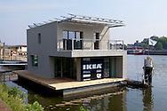.....das aldie benoetigte Energie (Gas, Strom und Wasser) selbst bereitstellt.   Das AutarkHome ist eine schwimmende, nachhaltige WohnunNLD, the Netherlands, Maastricht, Autarkhome, floating house on the banks of the river Meuse. The Autarkhome is the first self-sufficient floating passive house in the world. It needs no connections on the banks. It was designed by Pieter de Kromwijk from Coenegracht en Kromwijk  architects. This model house is furnished by IKEA. - ..NLD, Niederlande, Maastricht, Autarkhome, schwimmendes Haus am Ufer der Maas. Das Autarkhome ist das erste schwimmende Passivhaus der Welt. Das Haus ist komplett selbstversorgend und braucht keine Anschluesse auf dem Ufer. Der Entwurf stammt von Pieter Kromwijk von Coenegracht en Kromwijk Architekten. Diese Musterhaus wurde von IKEA ausgestattet.