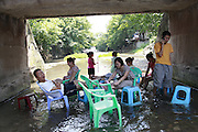 CHONGQING, CHINA - JULY 28: (CHINA OUT)<br /> <br /> Restaurants In A Stream<br /> <br /> Clients have lunch in a stream at Pianyan Ancient Town in Chongqing, China. Local restaurants put tables in a stream in summer to attract tourists. <br /> ©Exclusivepix