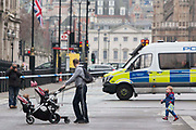UNITED KINGDOM, London: 23 March 2017 A man and his children walk in front of a cordon blocking access to Parliament Square this morning after a terror attack which killed four people including the attacker in Westminster yesterday. Rick Findler / Story Picture Agency