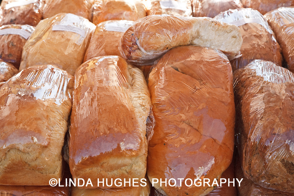 Plastic Wrapped Loaves of Bread at an Outdoor market