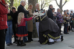 © Licensed to London News Pictures. 12/05/2012, London, UK.  A girl feeds coin to a Morris men dressed as a unicon as people watch a Morris dance at the South Bank by the National Theatre in London as Morris men from around the country gather in London for a Westminster Morris Men Day of Dance, Saturday, May 12, 2012. Photo credit : Sang Tan/LNP