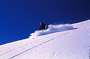 THIS PHOTO IS AVAILABLE FOR WEB DOWNLOAD ONLY. PLEASE CONTACT US FOR A LARGER PHOTO. Utah. Wasatch MTs, Linda Sjostrom in deep powder against blue sky.  MR