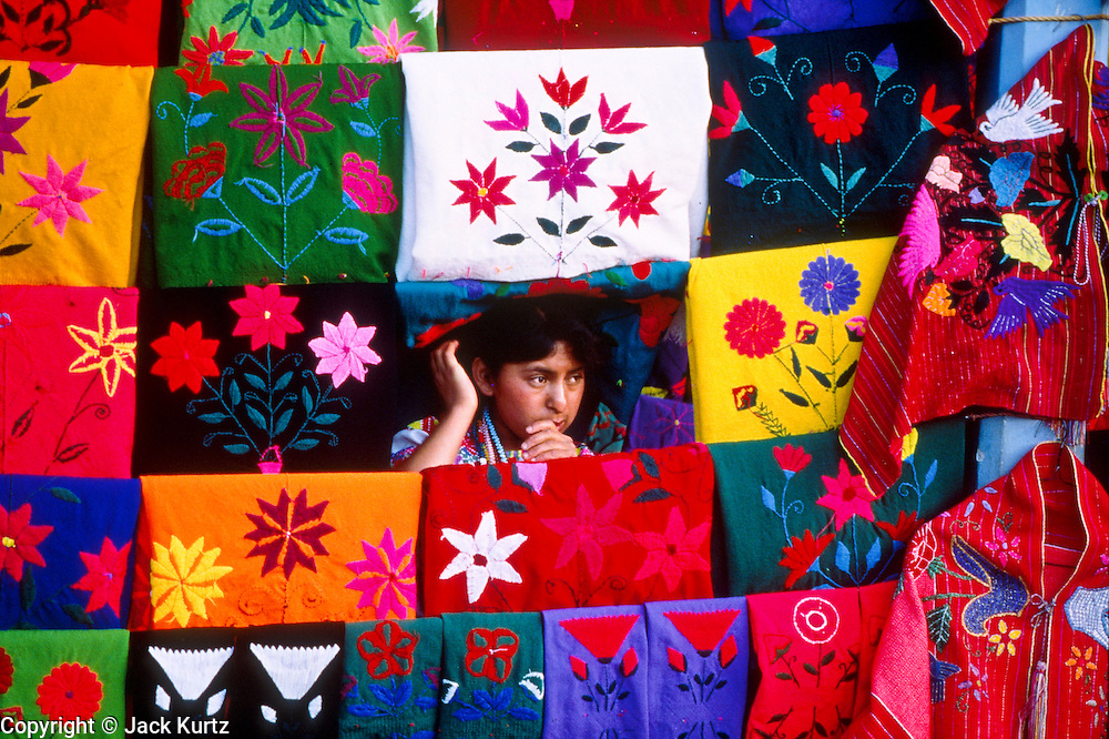 ZINACANTAN, CHIAPAS, MEXICO: A girl in the market in Zinacantan, Chiapas, Mexico, waits for tourists amidst the weavings she sells. The town is known for its textiles.  PHOTO © JACK KURTZ   TOURISM    INDIGENOUS   HUMAN RIGHTS   TRADE