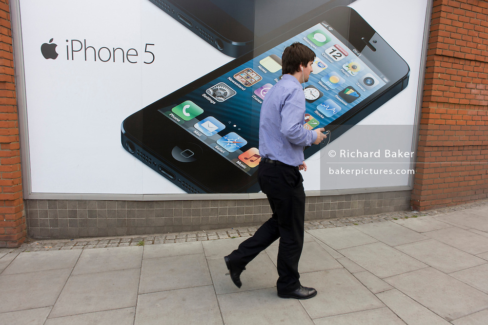 A man plugged in to earphones walks past a large poster for the iPhone 5 on the wall of a Carphone Warehouse retailer.