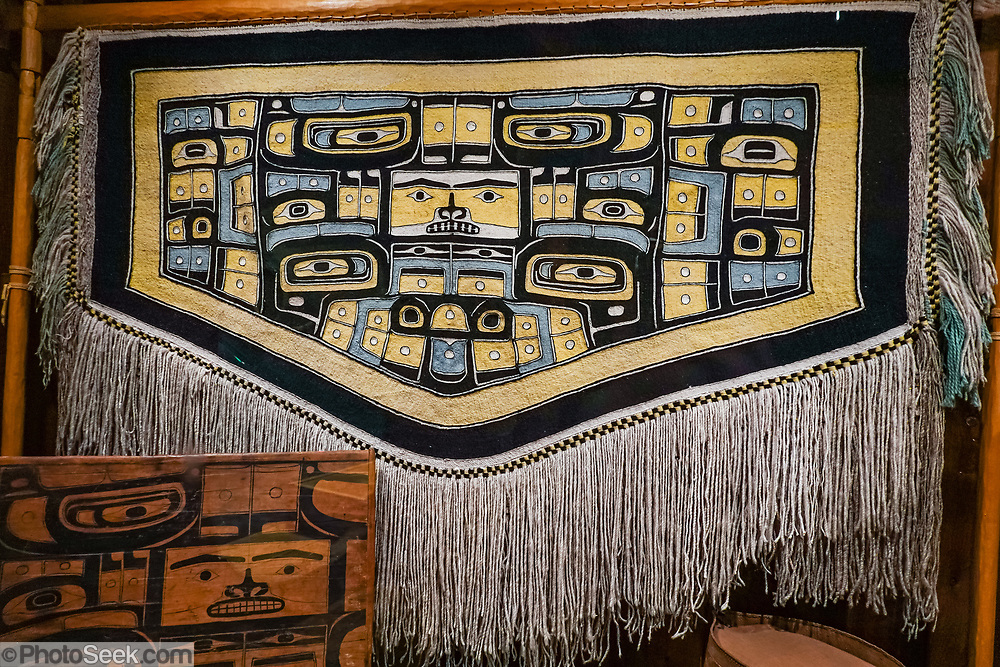 Sheet'ka Kwaan Tlingit ceremonial Chilkat robe (naaxein), a diving whale with head down and tail up in center panel in Alaska State Museum, Juneau, USA. The City and Borough of Juneau is the capital city of Alaska and the second largest city in the USA by area (only Sitka is larger). This unified municipality lies on Gastineau Channel in the Alaskan panhandle. Juneau has been the capital of Alaska since 1906, when the government of what was the District of Alaska was moved from Sitka. The city is named after a gold prospector from Quebec, Joe Juneau. Isolated by rugged terrain on Alaska's mainland, Juneau can only be reached by plane or boat. Downtown Juneau sits at sea level under steep mountains up to 4000 feet high, topped by Juneau Icefield and 30 glaciers.