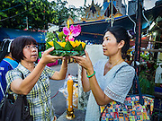 25 NOVEMBER 2015 - BANGKOK, THAILAND:  Thai woman pray before floating her krathong in the Chao Phraya River during Loy Krathong at Wat Yannawa in Bangkok. Loy Krathong takes place on the evening of the full moon of the 12th month in the traditional Thai lunar calendar. In the western calendar this usually falls in November. Loy means 'to float', while krathong refers to the usually lotus-shaped container which floats on the water. Traditional krathongs are made of the layers of the trunk of a banana tree or a spider lily plant. Now, many people use krathongs of baked bread which disintegrate in the water and feed the fish. A krathong is decorated with elaborately folded banana leaves, incense sticks, and a candle. A small coin is sometimes included as an offering to the river spirits. On the night of the full moon, Thais launch their krathong on a river, canal or a pond, making a wish as they do so.    PHOTO BY JACK KURTZ