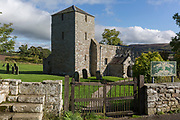 An exterior of St. John the Baptist Church in Edlingham with its fortified belfry to repel cross-border rievers, on 28th September 2017, Northumberland, England. St. John the Baptist Church is a Mediaeval (11th century) Church in Edlingham, Alnwick, Northumberland, England. The church is mostly Norman, from two periods, the late 11th - early 12th Century and late 12th century. The church is adjacent to Edlingham Castle, a 13th-century castle with 16th-century battlements and defences.