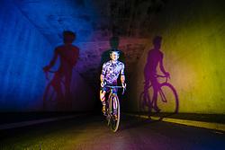 Cyclist Riding through Tunnel casting Shadows on Wall