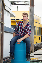 handsome man sitting on a barrel on a boat dock