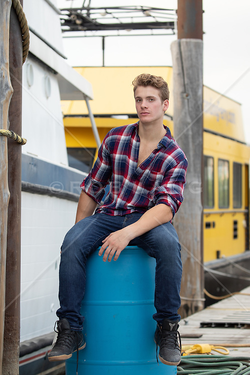 handsome man sitting on a barrel on a boat dock