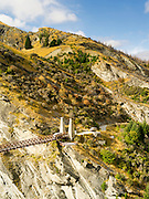 Two tourist buses from Queenstown Heritage Tours cross an old suspension bridge across the Shotover River and Skipper's Canyon, Queenstown, New Zealand