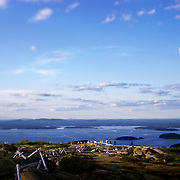 August, 2009 - Cadillac Mountain, Maine : Puffy white clouds float across a summery blue sky as the sun spot-lights a group of travelers atop Cadillac Mountain in Acadia National Park on Mt. Desert Island. The ocean and islands are apparent in the distance.