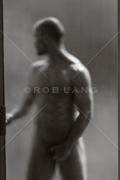 naked man standing outdoors by a sliding door