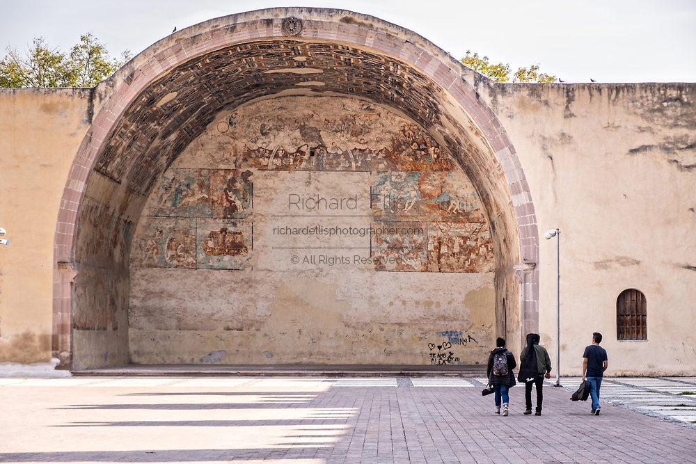 Students walk toward the original Indian Chapel at the San Nicolas Tolentino Temple and Ex-Monastery in Actopan, Hidalgo, Mexico. During colonial times the Roman Catholic church forbid indigenous people from entering the church until they were baptized.