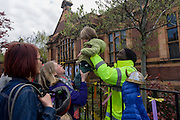 A security guard employed by Lambmeth mCmounmcmil mpasses a child over railings outside of the now closed Carnegie Library in Herne Hill, south London. The local community occupied their important resource for learning and social hub and after a long campaign but now Lambeth have gone ahead and closed the library's doors for the last time because they say, cuts to their budget mean millions must be saved. They plan to re-purpose it into a gym although details are unknown.