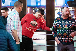 "© Licensed to London News Pictures . 21/12/2018 . Manchester , UK . A man wearing a Merry Christmas sweater vomits and slumps back against a window at the Printworks . Revellers out in Manchester City Centre overnight during "" Mad Friday "" , named for historically being one of the busiest nights of the year for the emergency services in the UK . Photo credit : Joel Goodman/LNP"