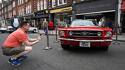 © Licensed to London News Pictures. 17/06/2018. LONDON, UK. A visitor views a 1965 GT Mustang Optioned Convertible at the 6th Annual Classic and Supercar Pageant held at St John's Wood High Street.  Traditionally taking place on Fathers' Day, the show brings together an eclectic mix of exotic and popular vehicles attracting visitors young and old and raises funds for the local charity, The St John's Hospice.  Photo credit: Stephen Chung/LNP