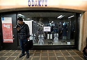 A man reads a book outside a department store that has switched off its lights to safe electricity in Tokyo, Japan  on 18 March, 2011, exactly one week after a magnitude 9 quake and mega-tsunami rocked the area in northeastern Japan. Residents and businesses throughout the nation's capital are being urged to save electricity to help the recovery effort of the nuclear plants in Fukushima. Photographer: Robert Gilhooly