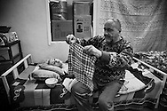 29.1.2015 Kirkuk, Iraq. Ganim Hormoz Gorgis 60 years old, prepares the usual meal of bread and milk for his boy Rony, 21, who has quadriplegia.