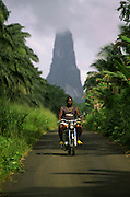 Man riding a motorbike on the road that leads to the south of Sao Tome island. At the distance Cao Grande (Big Dog) hill can be seen.