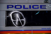 A police van is dawbed with the anarchist symbol - The annual Million Mask March bonfire night protest started in Trafalgar Square and headed to Westminster where it splintered. The march was organised by Anonymous UK and marchers wore the trademark V for Vendetta, Guy Fawkes masks. The police had placed tight restrictions on the route after trouble last year but, after a brief kettle, seemed happy to let the crowd filter in different directions.