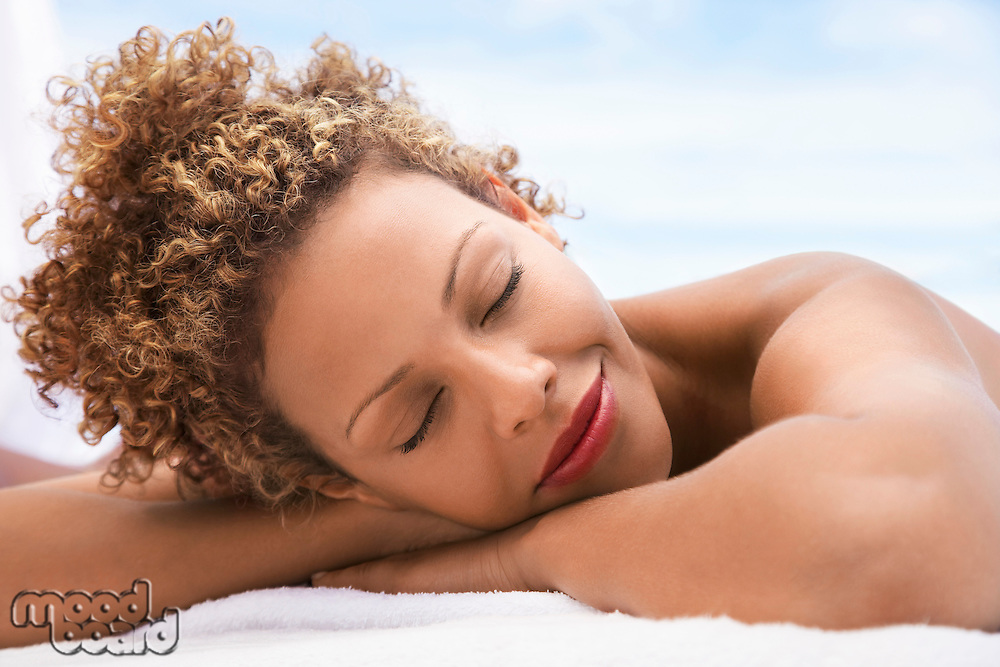 Woman lying on massage table head and shoulders eyes closed