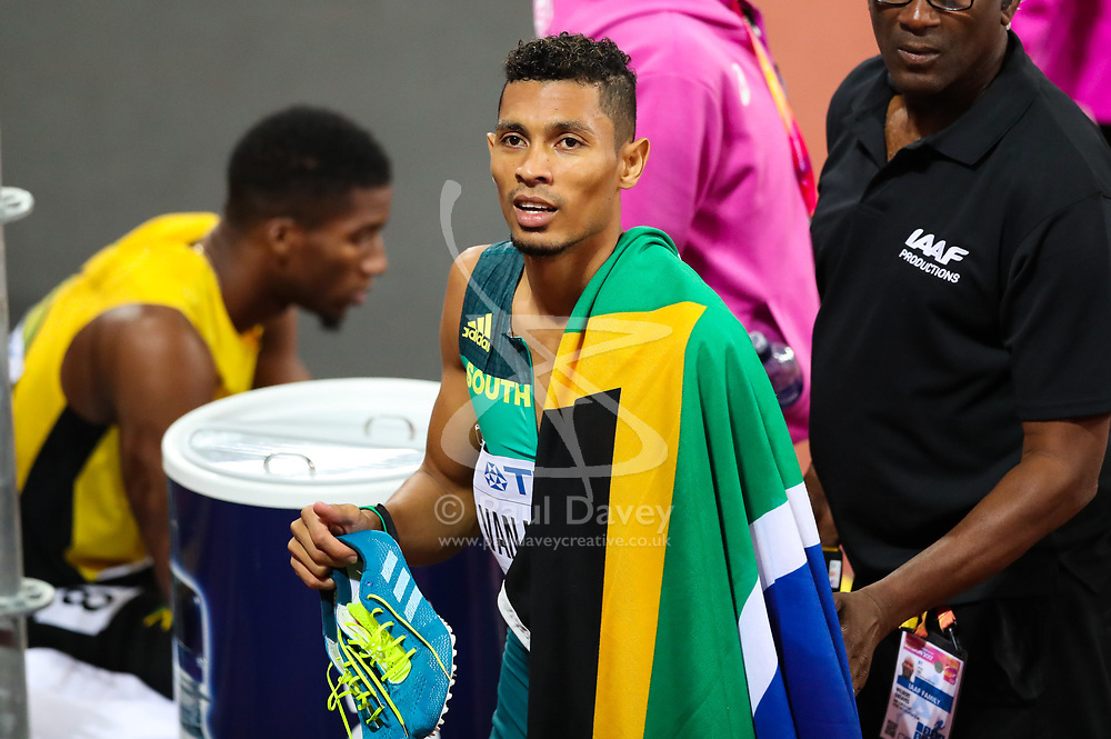 London, August 08 2017 . Wayde van Niekerk, South Africa, is draped in his country's flag after becoming world champion in the men's 400m final on day five of the IAAF London 2017 world Championships at the London Stadium. © Paul Davey.