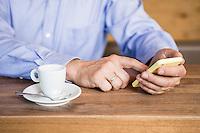 Österreich, Geschäftsmann mit Smartphone bei Kaffeepause an Theke in Restaurant, Casual Look, Detail Hände