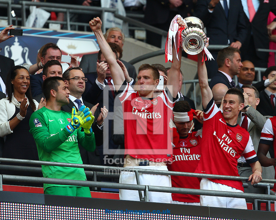 Laurent Koscielny ( R ) and Per Mertesacker ( C) of Arsenal lifts the trophy after his team win the The FA Cup Final match at Wembley Stadium, London<br /> Picture by Paul Terry/Focus Images Ltd +44 7545 642257<br /> 17/05/2014