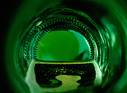"""Beauty at the Bottom: Lucky Night""- This image is a photograph of a beer bottle shot right down the mouth of the bottle. A television provides the main light source."