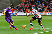 Chiedozie Ogbene (24) of Exeter City drives in to the 18 yard box with Harry Cardwell (17) of Grimsby Town closing in during the EFL Sky Bet League 2 match between Exeter City and Grimsby Town FC at St James' Park, Exeter, England on 29 December 2018.