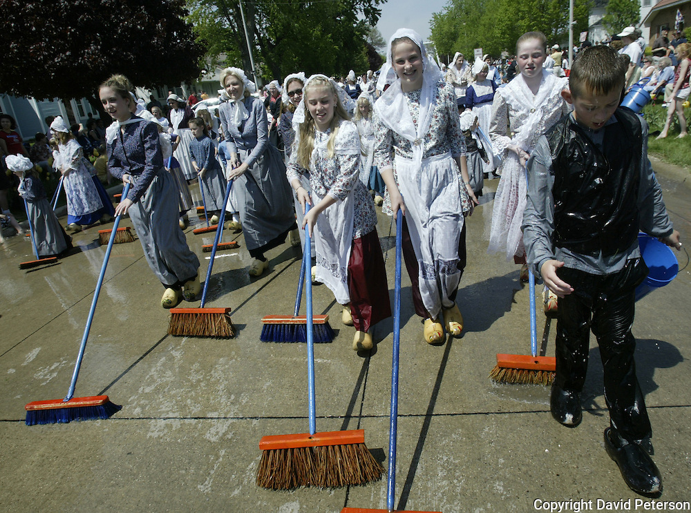 Tradition demands immaculately clean streets for the passage of the Queen and her Court in the Volksparade,  during the annual Orange City Tulip Festival in Orange City, Iowa, USA.  Boys dressed in tradtional Dutch costumes douse the street and themselves with buckets of water before girls follow behind with scrubbing brooms.  This event took place in April of 2004.