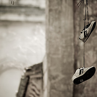 Gym shoes hanging from a laces in urban environment