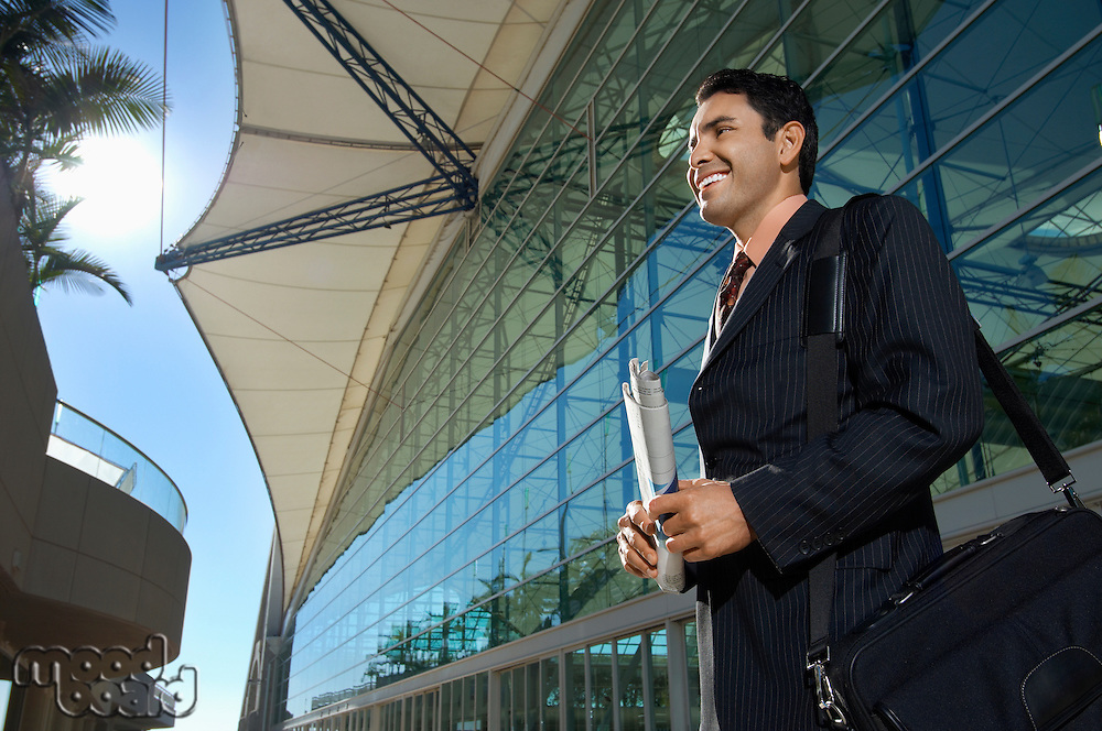 Businessman standing outside office building and smiling, low angle view