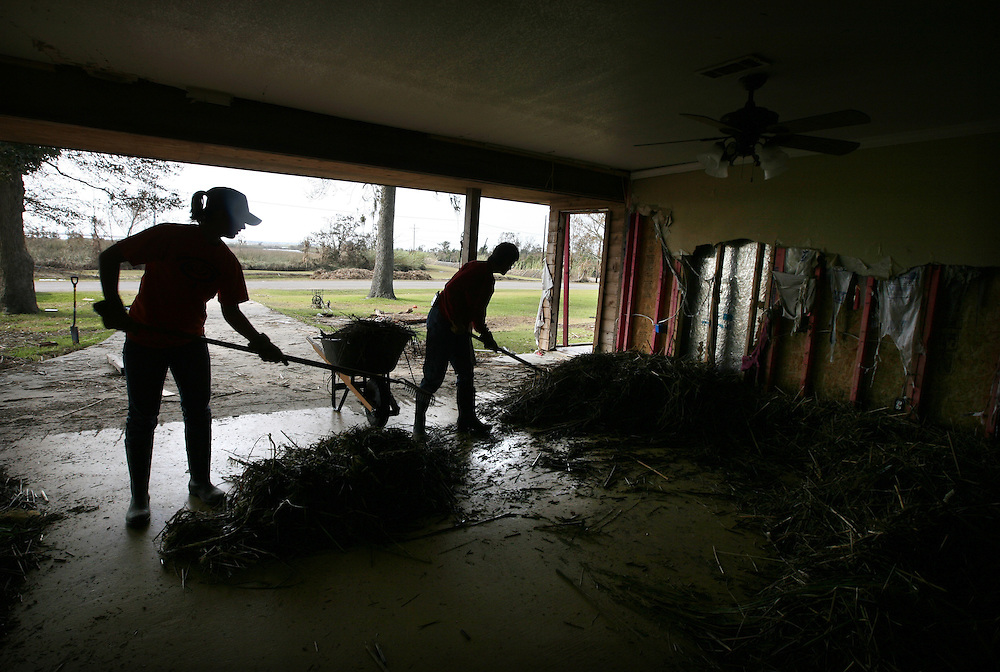 Robyn Cash, 20, left, and her mother Jana Cash of Beaumont remove marshland debris from the den of Jana's sister's home on Strapper Road in Bridge City, Texas, Thursday September 18, 2008.  A storm surge pushed water from the Sabine River directly through the home, destroying the entire front wall. So far the Cashes had removed 86 wheelbarrows of debris from the home.