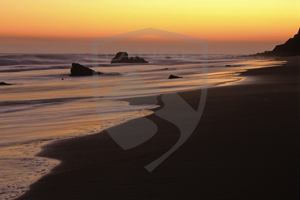 dramatic sunset light silhouettes the flowing pacific ocean tide in oranges and yellows at el matador beach in malibu southern california.