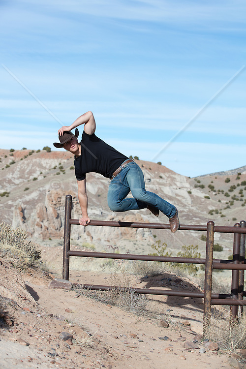 cowboy jumping over a fence on a rustic ranch