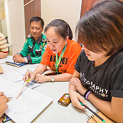 CAPTION: Members of Quezon City Climate Core Team meet to discuss potential ideas to include in their local climate change action plans. Although they have only recently become involved with ACCCRN, they have already shared ideas and best practices with other cities. For example, they are now thinking about starting an electric jeepney scheme and implementing various renewable energy systems. LOCATION: City Hall, Quezon City, Philippines. INDIVIDUAL(S) PHOTOGRAPHED: From left to right: Ronald Mallari, Magdalene Guevarra and Nadine Valderrama.