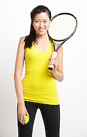 Portrait of happy Asian woman holding tennis ball and racket against white background