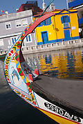 The painted bow of a Moliceiro boat with the background of traditional homes on the Canal de S. Roque, Aveiro, Portugal. Moliceiros are vessels circulating in the lagoon area of Rio Vouga, Aveira, originally used for the harvesting of seaweed but currently most used for tourism trips.