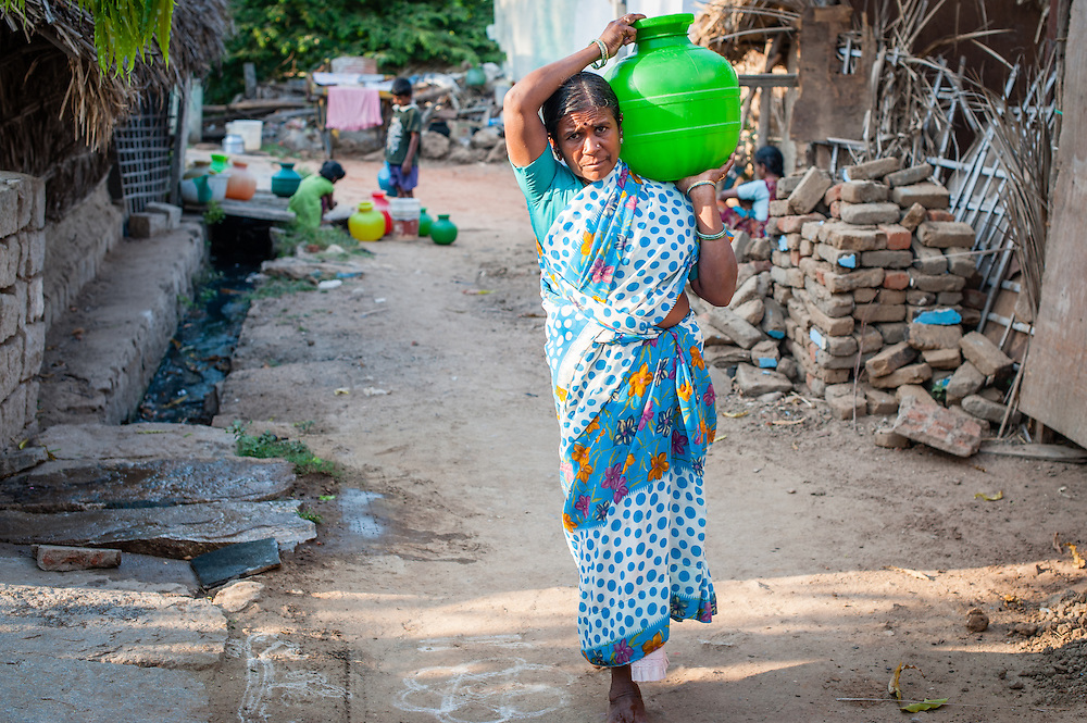 Indian woman in sari carrying water in plastic container (India)
