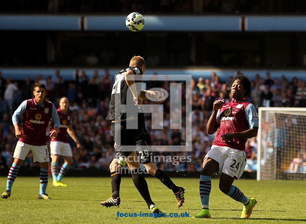 Michael Dawson (centre) of Hull City clears the ball away from Carlos S&aacute;nchez (right) of Aston Villa during the Barclays Premier League match at Villa Park, Birmingham<br /> Picture by Tom Smith/Focus Images Ltd 07545141164<br /> 31/08/2014