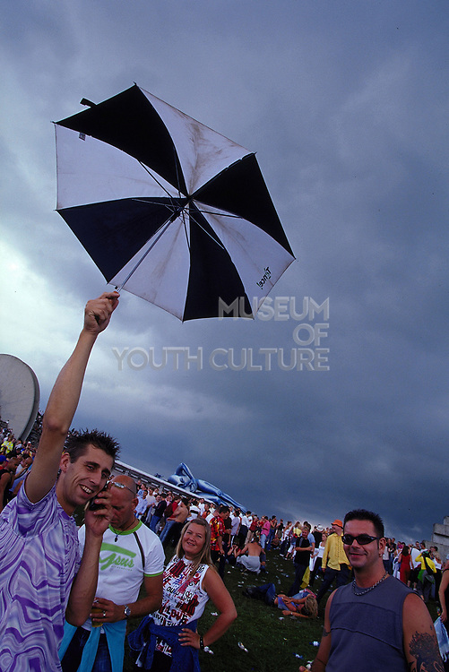 Man on mobile phone holding umbrella outside at Dance Valley Holland August 2002