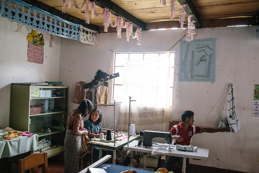 Students work in the sewing class at Centro de Formacion Nuevos Mayas in the Xix community. Many children of the farmers at the Parque Agro-Ecological Ixil, in Nebaj, Guatemala attend this school because of the extra income their parents make. The land, about 640 acres, was purchased by 75 farmers and in partnership with the Nature Conservancy and USAID who have taught them best agricultural practices, like how to diversify crops, and best practices in manufacturing, such as to keep crops from human contamination. After five years, the farmers have paid off 85 percent of the loan to purchase the land, and the farmers have been able to put their children through school and receive medical care as a result of the new income.