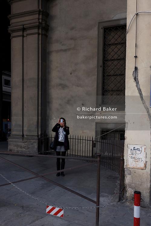 Single lady tourist takes pictures on camera phone near Piazza degli Uffizi.