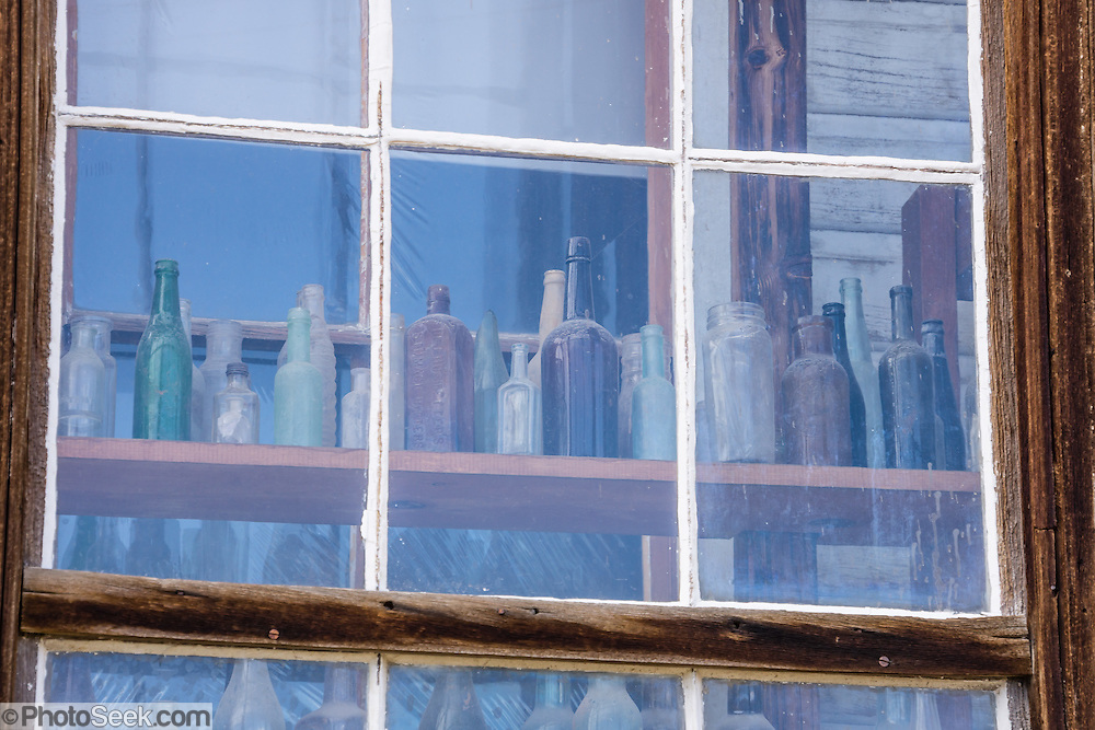 "Glass reflecting blue sky obscures rows of bottles seen behind. Bodie State Historic Park lies in the Bodie Hills east of the Sierra Nevada mountain range in Mono County, near Bridgeport, California, USA. After W. S. Bodey's original gold discovery in 1859, profitable gold ore discoveries in 1876 and 1878 transformed ""Bodie"" from an isolated mining camp to a Wild West boomtown. By 1879, Bodie had a population of 5000-7000 people with 2000 buildings. At its peak, 65 saloons lined Main Street, which was a mile long. Bodie declined rapidly 1912-1917 and the last mine closed in 1942. Bodie became a National Historic Landmark in 1961 and Bodie State Historic Park in 1962."